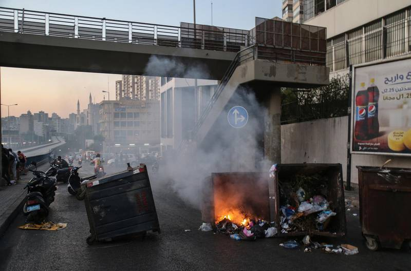 epa09304077 Anti-government protesters burn waste bins to block a highway that leads to the airport during a protest in Beirut, Lebanon, 26 June 2021. Anti-government protesters closed the streets with garbage bins and burning tires, to protest against power cuts, high cost of living, low purchasing power of the Lebanese pound, as well as the failure of political leaders to form a government after months of deadlock. State-provided electricity in Beirut has reached record-low levels that seem insurmountable for financial reasons.  EPA/NABIL MOUNZER