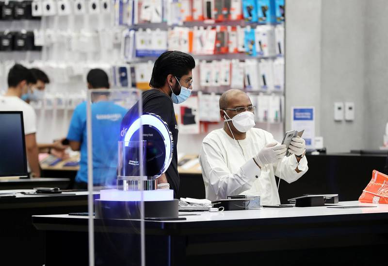 DUBAI, UNITED ARAB EMIRATES , April 29 – 2020 :- Shoppers wearing protective face mask to prevent the spread of the coronavirus at the Samsung store at Mall of the Emirates in Dubai. Authorities ease the restriction for the residents in Dubai. At present mall opening timing is 12:00 pm to 10:00 pm. Carrefour timing is 9:00 am to 10:00 pm. (Pawan Singh / The National) For News/Standalone/Online. Story by Patrick