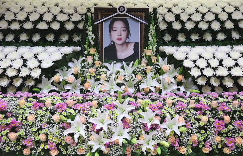 TOPSHOT - The portrait of late K-pop star Goo Hara is seen surrounded by flowers at a memorial altar at a hospital in Seoul on November 25, 2019. Fans mourned and questions were asked November 25 after K-pop star and revenge porn victim Goo Hara was found dead in a possible suicide, which would make her the second female singer in a month to take her own life in the high-pressure industry. - South Korea OUT  / AFP / Dong-A Ilbo / str