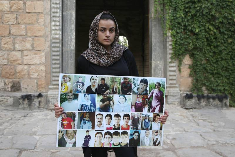 Yazidi woman Ashwaq Haji, allegedly used by the Islamic State group (IS) as a sex slave, holds portraits of jihadists' victims from her village of Kocho near Sinjar, as she visits the Lalish temple, in Lalish, northern Iraq, on August 15, 2018. - A young Yazidi woman who fled to Germany but returned home to northern Iraq says she cannot escape her Islamic State group captor who held her as a sex slave for three months.  Ashwaq Haji, 19, says she ran into the man in a German supermarket in February. Traumatised by the encounter, she returned to Iraq the next month. Like many other Yazidis, she was kidnapped by IS when the jihadists seized swathes of Iraq in the summer of 2014. (Photo by - / AFP)