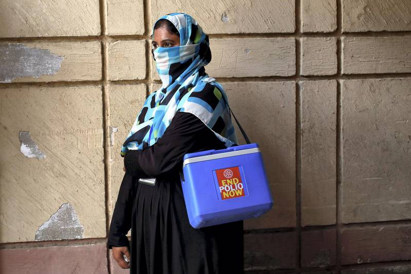 A vaccinator with kit box, waits for her colleagues, to do an anti-polio campaign in a low-income neighbourhood in Karachi, Pakistan April 9, 2018. REUTERS/Akhtar Soomro