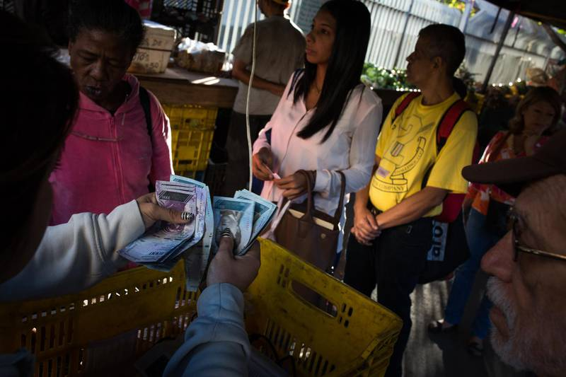 A vendor counts Bolivar banknotes received from a customer at a vegetable stand in Caracas, Venezuela, on Thursday, March 1, 2018. Inhyper-inflationaryVenezuela, paper money is a scarce commodity but a necessity. A popular means of obtaining bolivar banknotes is from 'cash dealers' who charge clients a 100 % premium fee. Photographer: Wil Riera/Bloomberg