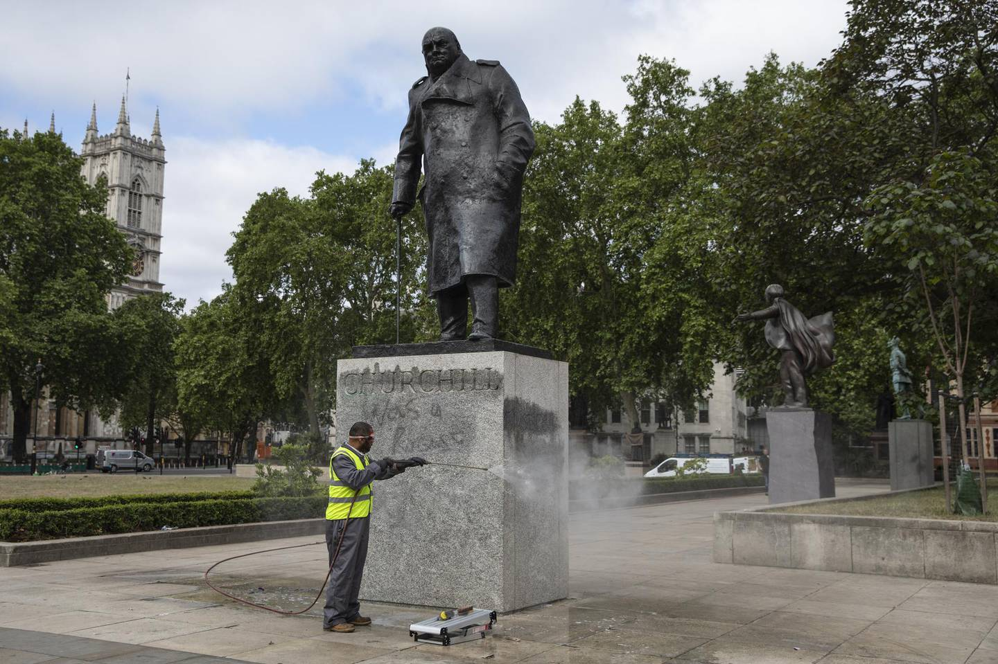 """LONDON, ENGLAND - JUNE 08: A worker cleans the Churchill statue in Parliament Square that had been spray painted with the words 'was a racist' on June 08, 2020 in London, England. Outside the Houses of Parliament, the statue of former Prime Minister Winston Churchill was spray-painted with the words """"was a racist"""" amid anti-racism protests over the weekend. In Bristol, protesters toppled a statue of Edward Colston, a 17th-century slave-trader, and tossed it into the harbor. (Photo by Dan Kitwood/Getty Images)"""