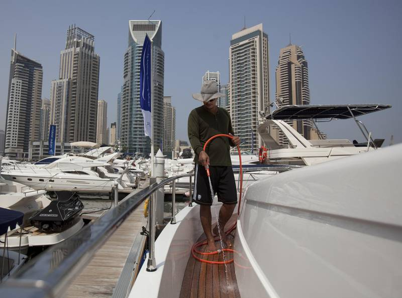 August 27, 2011 - Ronald from the Philippines hoses down a San Lorenzo 62 yacht in Dubai Marina. Ronald says he washes the boat almost everyday which is for sale for 8million Dhs by a Russian owner. Ronald says he enjoys the freedom his job gives him and enjoys the time he can spend out on the sea at times. Pawel Dwulit