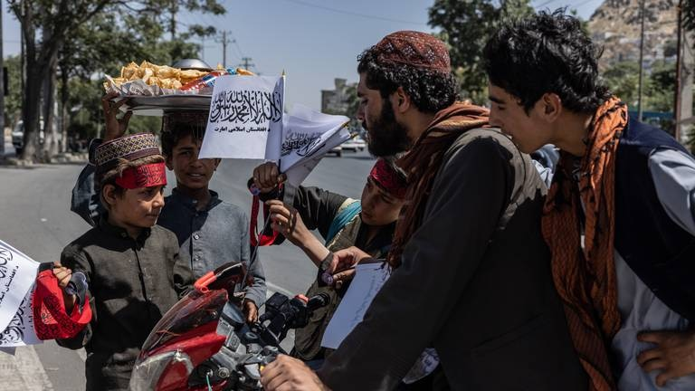 An image that illustrates this article Taliban fighters eat ice cream as a slowly changing Kabul watches a month on