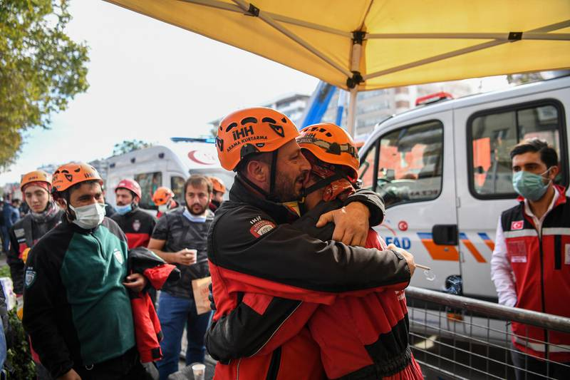 Ahmet Celik (R) and Ibrahim Topal (L) from Turkey's Humanitarian Relief Foundation (IHH) rescue and search team embrace after rescuing Ayda Gezgin, a three-year-old survivor from a collapsed building in Izmir on November 3, 2020, following a 7.0-magnitude quake which struck the Aegean port city on October 30. - Rescue workers were searching eight buildings in Izmir despite dwindling hope for survivors. The death toll from the quake rose to 102 in Turkey on November 3, the Turkish emergency authority AFAD reported, with 1,026 people injured of which 147 remain in hospital. (Photo by Ozan KOSE / AFP)