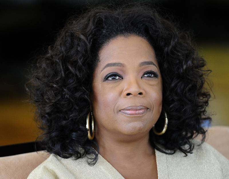 (FILES) In this file photo taken on January 13, 2012 US talk show queen Oprah Winfrey looks on as she answers to journalist's questions at her South African girls' academy on January 13, 2012 in Henley on Klip.  Television personality Oprah Winfrey has agreed to produce shows for Apple as the iPhone maker prepares to make a push into original content. / AFP / STEPHANE DE SAKUTIN