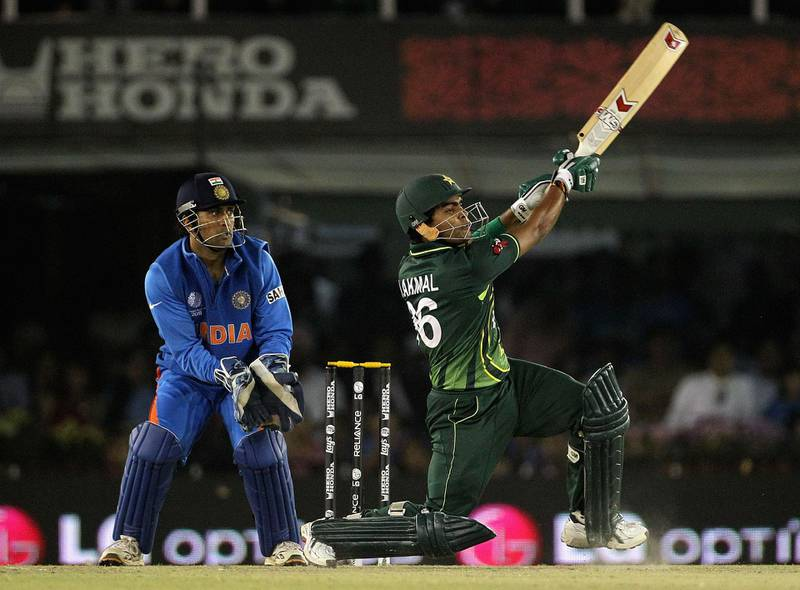 MOHALI, INDIA - MARCH 30:  Umar Akmal of Pakistan hits a six over mid wicket with MS Dhoni of India looking on during the 2011 ICC World Cup second Semi-Final between Pakistan and India at Punjab Cricket Association (PCA) Stadium on March 30, 2011 in Mohali, India.  (Photo by Hamish Blair/Getty Images)