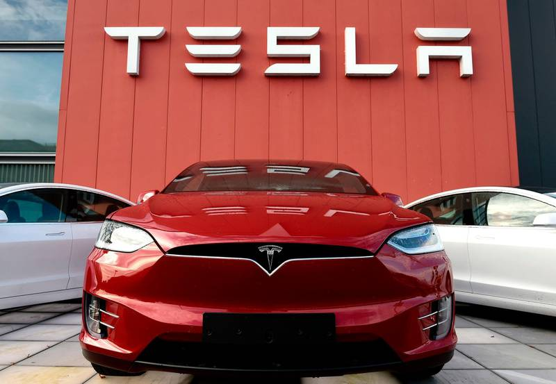 """(FILES) In this file photo taken on October 23, 2019 cars and a logo are pictured at the showroom and service center for the US automotive and energy company Tesla in Amsterdam. Tesla CEO Elon Musk announced on November 12, 2019 in Berlin the construction of a new """"gigafactory"""" in the outskirts of the German Capital city. / AFP / John THYS"""