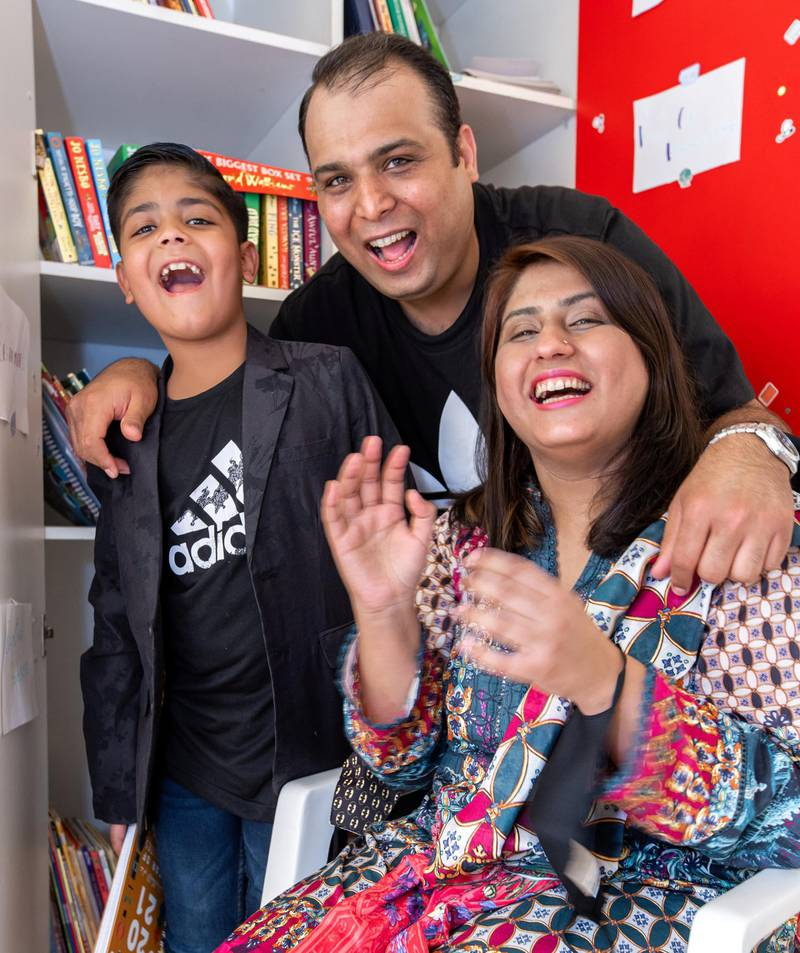 Ayaan Tariq, 7, with parents, Tariq and Moomal. He has a collection of around 300-400 books which he keeps in a cupboard. He lends these out to children free of charge. June 22, 2021. Victor Besa / The National.Reporter: Anam Rizi for News
