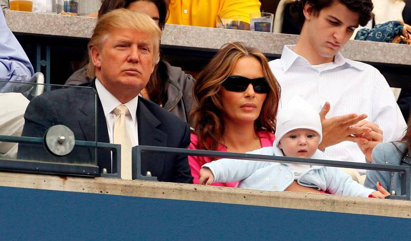epa00814832 Donald Trump sits with his wife Melania (R) as she holds their son Barron William Trump as they watch Andy Roddick of the US play Roger Federer of Switzerland during the men's final on the final day of the 2006 US Open tennis tournament in Flushing Meadows, New York Sunday 10 September 2006.  EPA/JASON SZENES