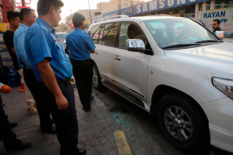 Security forces investigate a vehicle at the site of the assassination of Soad al-Ali, who has been involved in organizing protests demanding better services in the city, in the southern city of Basra, Iraq, Tuesday, Sept. 25, 2018. A police official said masked gunmen shot dead al-Ali, a mother of four, outside a supermarket. The gunmen fled the scene after shooting at her and her husband in their car. (AP Photo/Nabil al-Jurani)