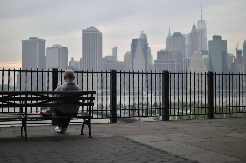 A man sits in the Brooklyn Heights Promenade overlooking the Manhattan skyline, in New York City on May 17, 2018. / AFP / HECTOR RETAMAL