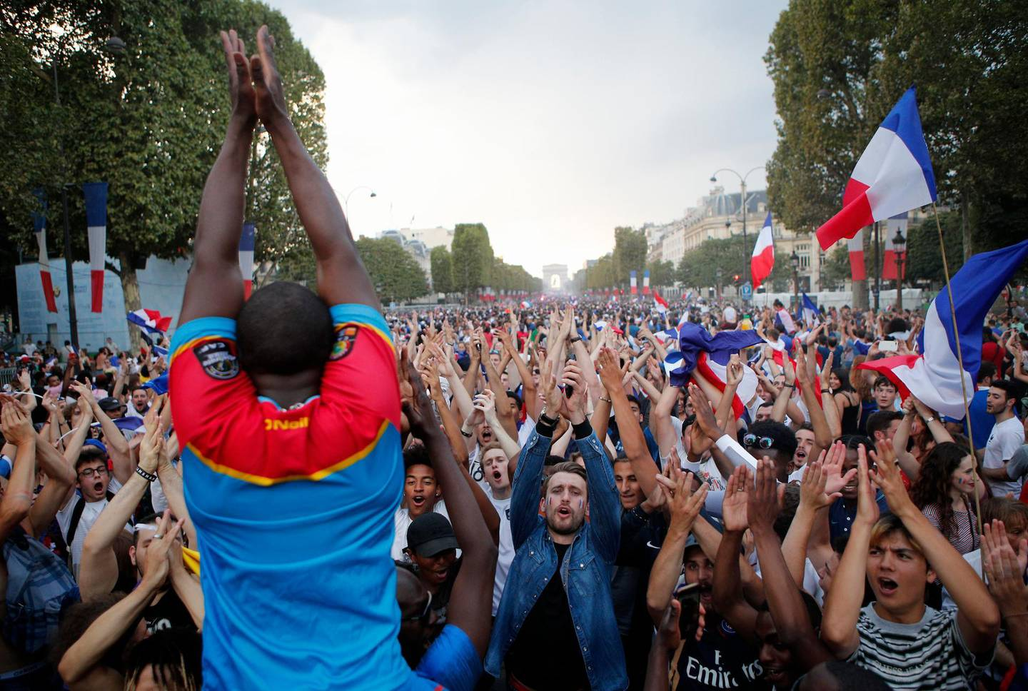 People clap their hands on the Champs Elysees avenue after France won the soccer World Cup final match between France and Croatia, Sunday, July 15, 2018 in Paris. France won its second World Cup title by beating Croatia 4-2 . (AP Photo/Francois Mori)
