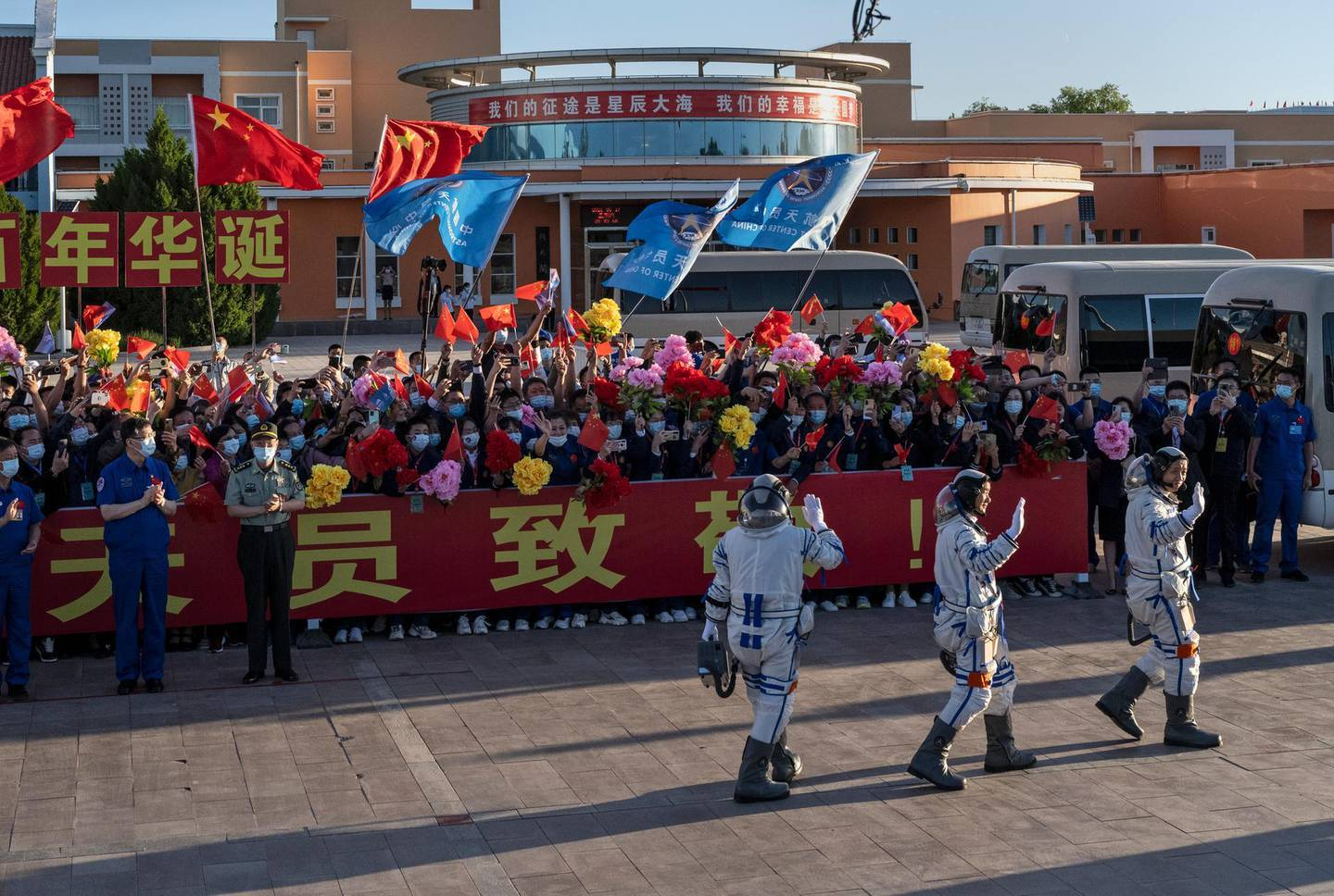 JIUQUAN, CHINA - JUNE 17: Chinese astronauts from China's Manned Space Agency, right to left, Nie Haisheng, Liu Boming, and Tang Hongbo wave at a departure ceremony before the launch of the Senzhou-12 at the Jiuquan Satellite Launch Center on June 17, 2021 in Jiuquan, Gansu province, China. The crew of the Shenzhou-12 spacecraft will be carried on the Long March-2F rocket launched to the space station China is building from the Gobi Desert marking the country's first manned mission in nearly five years. (Photo by Kevin Frayer/Getty Images)