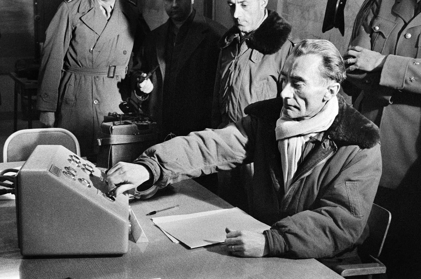 """Photo taken on December 27, 1960 of General Jean Thiry pressing the button which triggers the explosion of the third French atomic bomb on the test polygon at Reggane in the Sahara during the operation called """"Gerboise rouge"""". - General Jean Thiry, director of nuclear experiment centers, during the first French thermonuclear device in the Pacific in 1968, died on December 14 in Paris at the age of 84. AFP PHOTO (Photo by - / AFP)"""