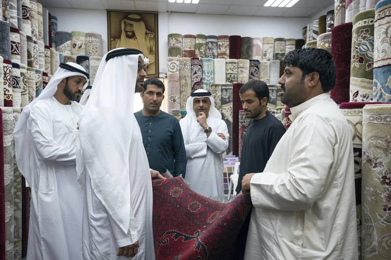 ABU DHABI, UNITED ARAB EMIRATES -  February 22, 2018: HH Sheikh Mohamed bin Zayed Al Nahyan, Crown Prince of Abu Dhabi and Deputy Supreme Commander of the UAE Armed Forces (2nd L), looks at a carpet at the Al Safa Carpet shop, in the carpet market of the Mina Zayed Port. Seen with HE Mohamed Mubarak Al Mazrouei, Undersecretary of the Crown Prince Court of Abu Dhabi (back L), and HE Jassem Mohamed Bu Ataba Al Zaabi, Chairman of Abu Dhabi Executive Office and Abu Dhabi Executive Council Member (back C).  ( Ryan Carter for the Crown Prince Court - Abu Dhabi ) ---
