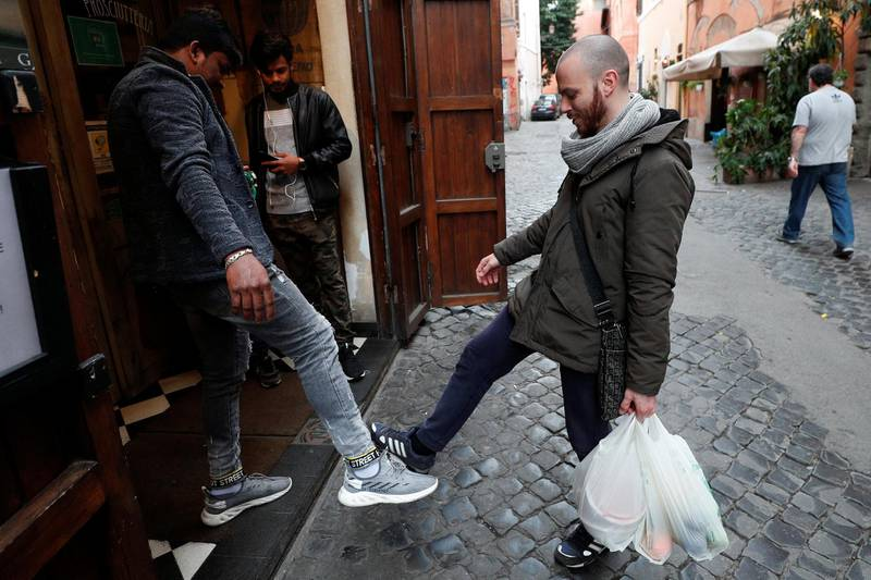 People salute using their feet to avoid contact, after a decree orders for the whole of Italy to be on lockdown in an unprecedented clampdown aimed at beating the coronavirus, in Trastevere area, Roma Italy, March 10, 2020. REUTERS/Guglielmo Mangiapane