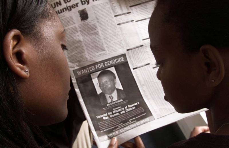 """FILE PHOTO: Readers look at a newspaper June 12, 2002 in Nairobi carrying the photograph of Rwandan Felicien Kabuga wanted by the United States. The United States published a """"wanted"""" photograph in Kenyan newspapers of the businessman accused of helping finance the 1994 killings in Rwanda REUTERS/George Mulala/File Photo"""