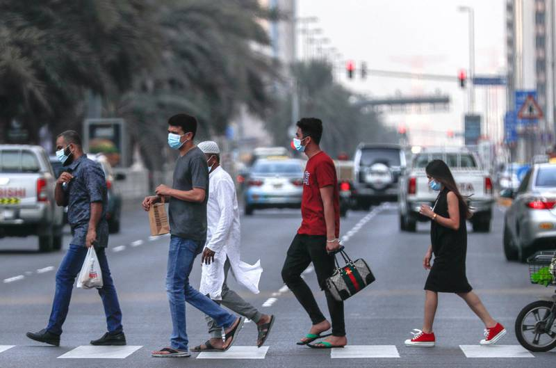 Abu Dhabi, United Arab Emirates, August 14, 2020.  Pedestrians with face masks cross the street at downtown Abu Dhabi on an early Friday evening.Victor Besa /The NationalSection:  NAFor:  Standalone/Stock Images