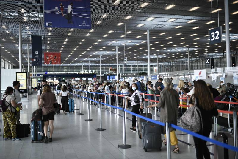 """(FILES) In this file photo taken on August 1, 2020, Travelers, wearing protective face masks, line up at the Orly Airport, south of Paris during a major weekend of the French summer holidays. Airlines need up to another $80 billion to survive, the head of the industry's trade association told a French daily on November 20, 2020, as many countries tighten restrictions to confront another wave of coronavirus infections. """"For the coming months the industry is estimated to need $70-$80 billion in additional aid,"""" the head of the International Air Transport Association (IATA) Alexandre de Juniac told La Tribune. """"Otherwise they won't survive."""" / AFP / STEPHANE DE SAKUTIN"""