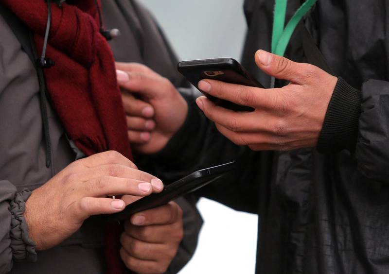 People hold smartphones in their hands while walking outside along a street in the Iranian capital Tehran on November 23, 2019. - Iranians have been struggling to adjust to life offline almost one week into a near-total internet blackout imposed amid violent demonstrations that has forced some to resort to old ways to get by. (Photo by ATTA KENARE / AFP)