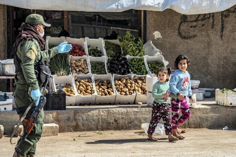 A member of the Kurdish Internal Security Forces of Asayesh urges children to return home, in Syria's northeastern city of Hasakeh on April 30, 2020, following measures taken by the Kurdish-led local authorities there, to limit the spread of the novel coronavirus. (Photo by DELIL SOULEIMAN / AFP)