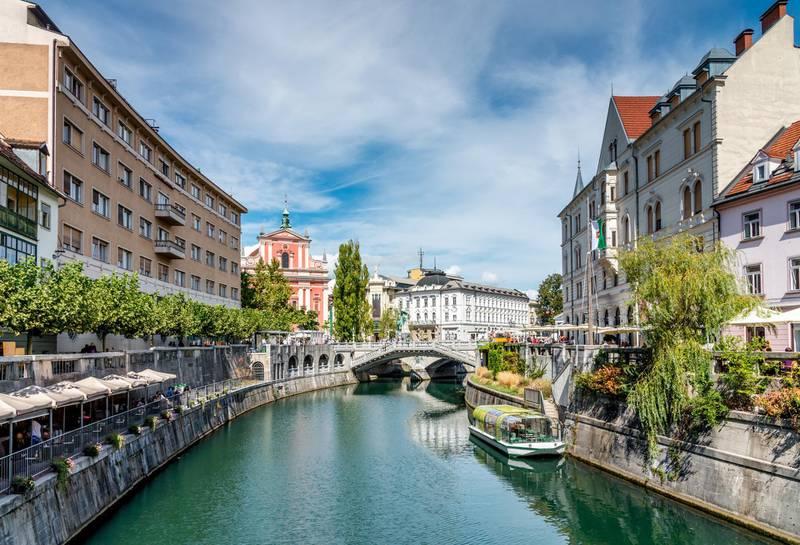 Beautiful crowded downtown Ljubljana City with Bars and Restaurants along the Ljubljanica River. View to the famous Tromostovje - Triple Bridge in Summer.  Ljubljana, Slovenia