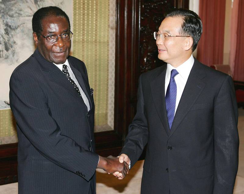 BEIJING - JULY 27:  Chinese Premier Wen Jiabao (R) geets Zimbabwe President Robert Mugabe on July 27, 2005 in Beijing, China. Following sanctions and isolation from Western countries over Mugabe's disastarous and criminal political reforms, Zimbabwe has turned to Asia, seeking to buttress political and trade relations in particular with China, Malaysia and Singapore. (Photo by Guang Niu/Getty Images)