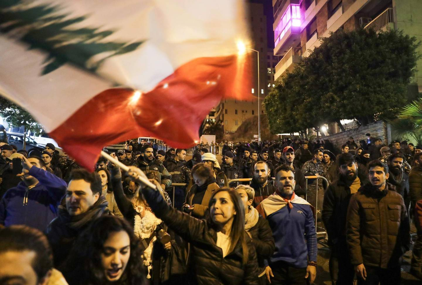 Lebanese protesters wave the national flag as they gather outside the house of Lebanon's new prime minister in the capital Beirut, calling for resignation less than 10 days after he was appointed, on December 28, 2019.  Protests continued after the resignation of the previous prime minister, while political parties negotiated for weeks before nominating Hassan Diab, a professor and former education minister, to replace him on December 19.  / AFP / ANWAR AMRO