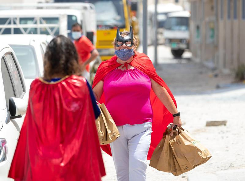 Ibtihal Makmahi-Tarik with Nicky Putter (R). Women dressed as superheroes handed out food, water, toiletries and water bottles at a labour camp in Al Quoz, Dubai on June 25th, 2021. Chris Whiteoak / The National.  Reporter: N/A for News