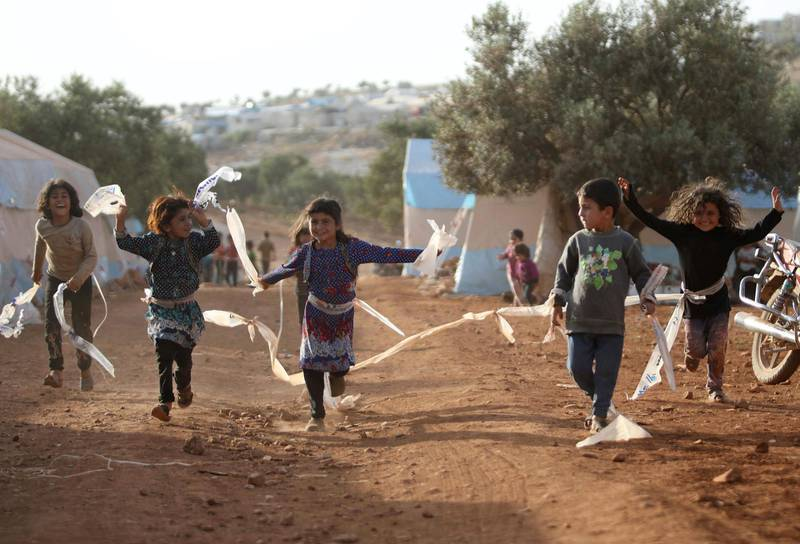 Displaced Syrian children play in a camp for internally displaced people near Kah, in the northern Idlib province near the border with Turkey on June 3, 2019 on the eve of Eid al-Fitr, which marks the end of the Muslim holy fasting month of Ramadan. The conflict in Syria has killed more than 370,000 people and displaced millions since it started in 2011. / AFP / Aaref WATAD
