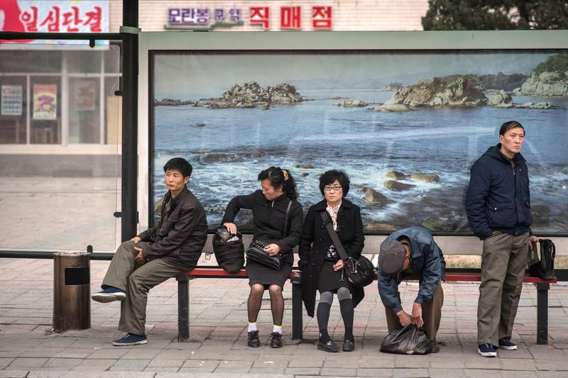 In a photo taken on April 8, 2017 commuters wait at a bus stop in Pyongyang. Buses are by far the most common means of public transport in the capital of around three million people, where access to private cars is rare, and offer the most extensive network. Tickets cost 5 won each – less than 0.1 US cents at free-market rates, making journeys virtually free. The city is one where everyone almost always appears to have a purpose, whether going to or from work, or taking part in some kind of group activity. At bus stops, though, commuters are forced to disrupt that process as they wait for a vehicle. It is a moment that reveals their private interests – whether talking to friends and colleagues, pensively watching the world go by, or sometimes playing with a smartphone. / AFP PHOTO / Ed JONES