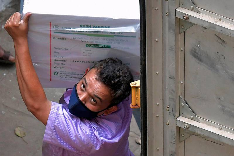 Workers transfer carton boxes of a Covishield vaccine developed by Pune based Serum Institute of India (SII) that arrived in a truck into the Karnataka Health Department cold storage facility in Bangalore on January 12, 2021, in preparation for the first round of vaccination drive scheduled to begin across the country from January 16. / AFP / Manjunath Kiran
