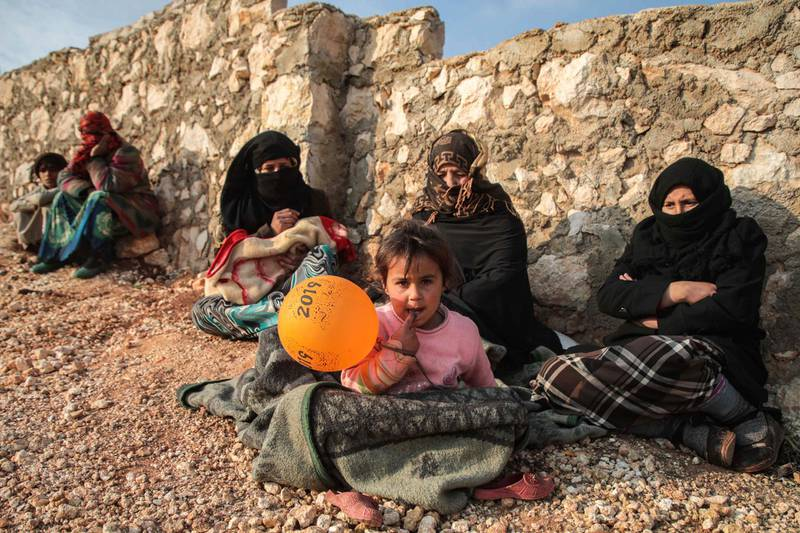 Displaced Syrians from the south of Idlib province sit out in the open in the countryside west of the town of Dana in the northwestern Syrian region on December 23, 2019. (Photo by Aaref WATAD / AFP)