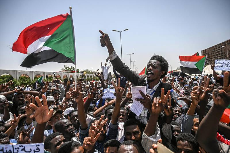 Sudanese protesters wave national flags as they chant slogans during an a sit-in outside the army headquarters in the capital Khartoum on April 26, 2019. - Protesters have massed outside the army complex in central Khartoum since April 6, initially to demand the overthrow of longtime leader Omar al-Bashir. But since his ouster by the army on April 11, the protesters have kept up their sit-in, demanding that the military council that took over hand power to a civilian administration. (Photo by OZAN KOSE / AFP)