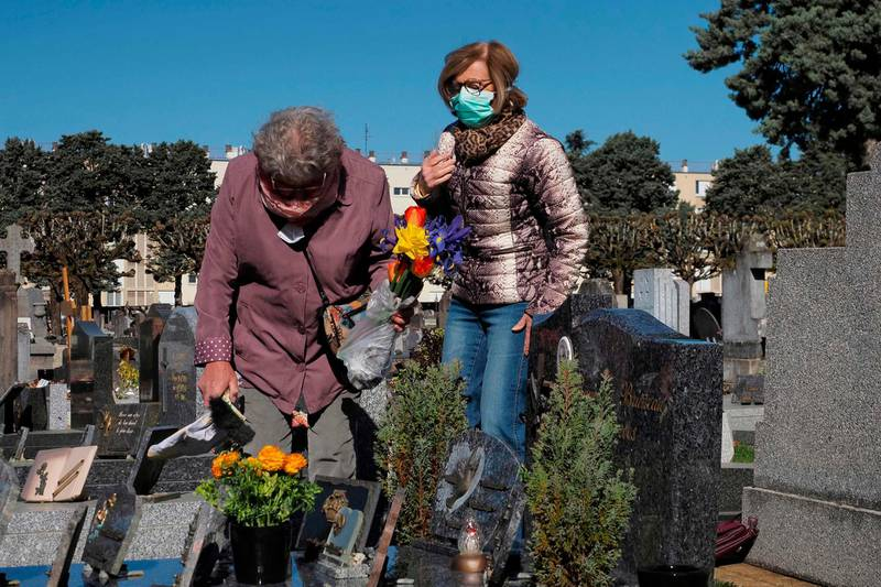 Two women wearing face masks lay flowers on a grave in Tours Saint-Symphorien cemetery, exceptionally open for Palm Sunday (Dimanche des Rameaux) on April 5, 2020, on the twentieth day of a lockdown in France aimed at curbing the spread of the COVID-19 infection caused by the novel coronavirus. / AFP / GUILLAUME SOUVANT