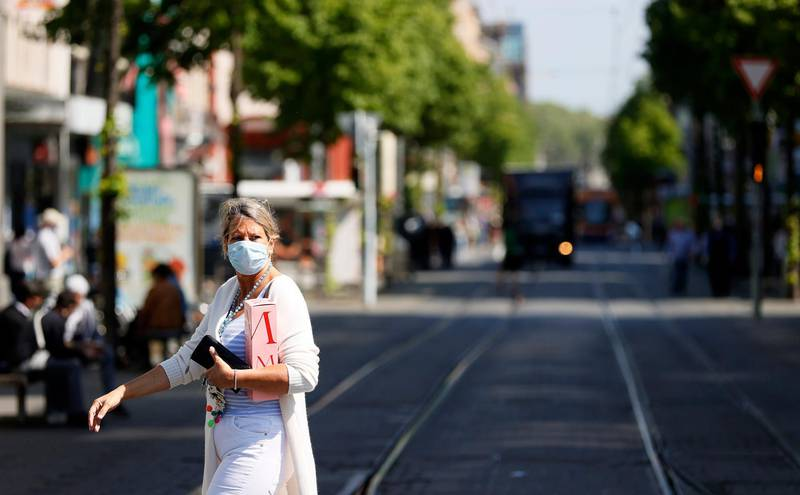 epa08386552 A woman wearing a protective face mask walks on the so-called 'Planken' street in Mannheim, Germany, 27 April 2020, amid the ongoing coronavirus COVID-19 pandemic. From today on, the wearing of face masks is obligatory in Baden-Wuerttemberg and other federal states in Germany. Countries around the world are taking increased measures to stem the widespread of the SARS-CoV-2 coronavirus which causes the COVID-19 disease.  EPA/RONALD WITTEK