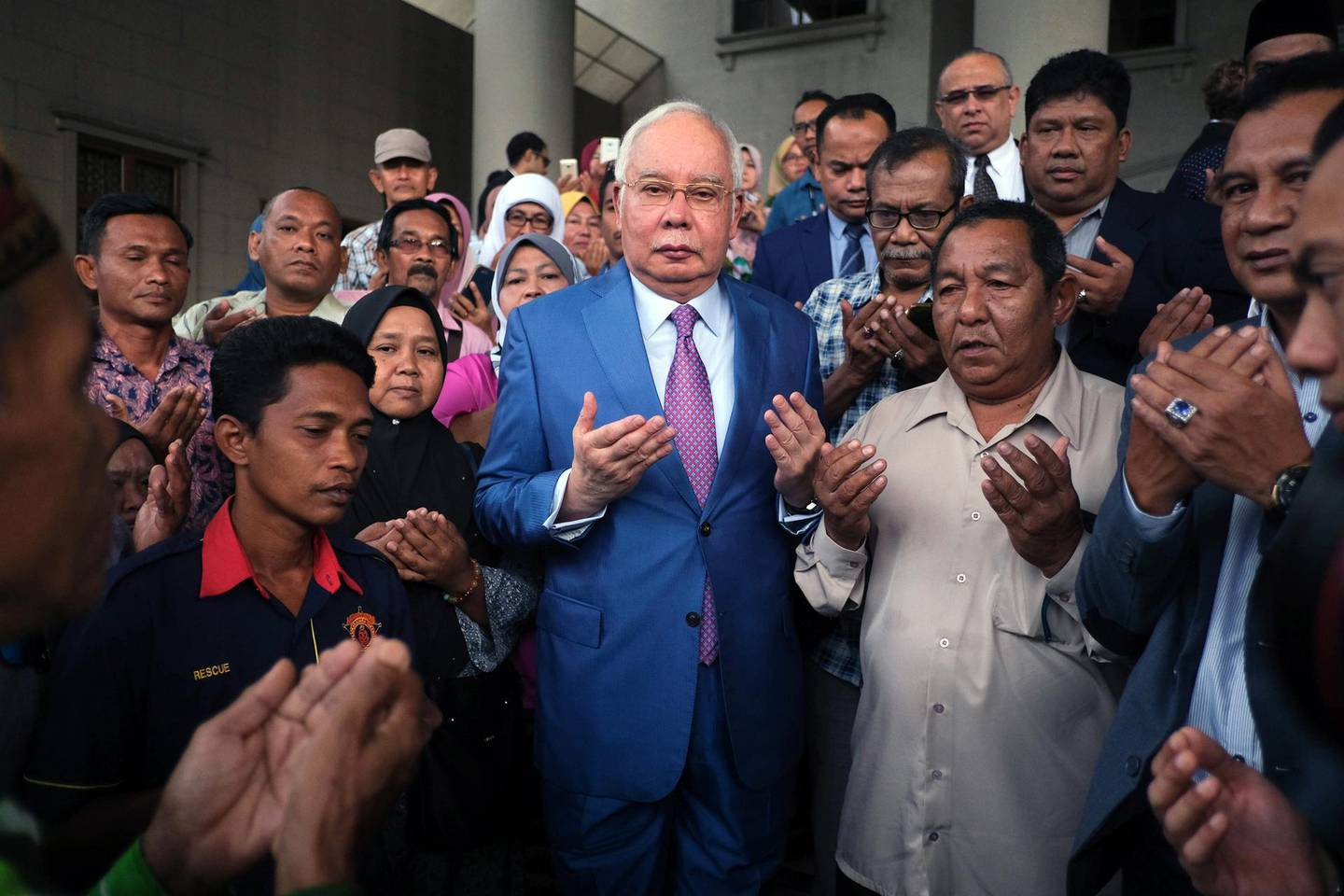 Najib Razak, Malaysia's former prime minister, center, offers prayers with his supporters as he arrives at the Kuala Lumpur Courts Complex in Kuala Lumpur, Malaysia, on Tuesday, Dec. 3, 2019. Najib is set to give his testimony to defend himself against charges of corruption involving a former 1MDB unit. Photographer: Samsul Said/Bloomberg