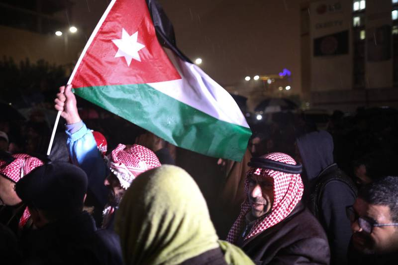 epa07213194 Jordanians hold their national flags and shout slogans as they demand the government for reforms in various fields during a protest under a heavy rain, in Amman, Jordan, 06 December 2018. A few hundred protesters gathered in the area leading to the Prime Minister office in central Amman, to demand political and economic reforms. The last time such protests took place, earlier in the summer, they had led to a change of government.  EPA/ANDRE PAIN