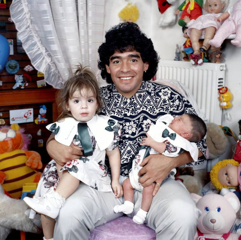 Argentinian football player Diego Armando Maradona sitting in a small bedroom with his daughters Dalma e Giannina in his arms. Italy, 1989 (Photo by Rino Petrosino/Mondadori via Getty Images)
