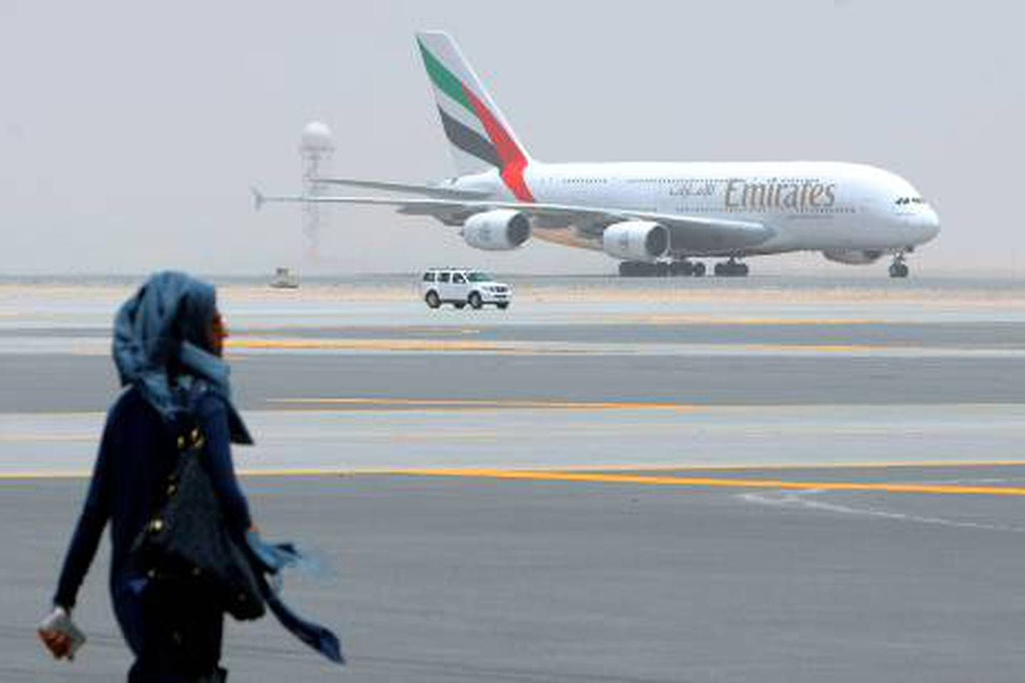 """A woman walks in front of an Emirates Airlines plane which landed on the runway during the media tour of Dubai's new second airport, Dubai World Central or Al-Maktoum International, operational only to cargo until passenger facilities are completed, on July 1, 2010, in the desert on the outskirts of the Gulf emirate, where a 32 million dollar (26 million euro) new """"city"""" is being built to include a port.  AFP PHOTO/KARIM SAHIB *** Local Caption ***  919076-01-08.jpg"""