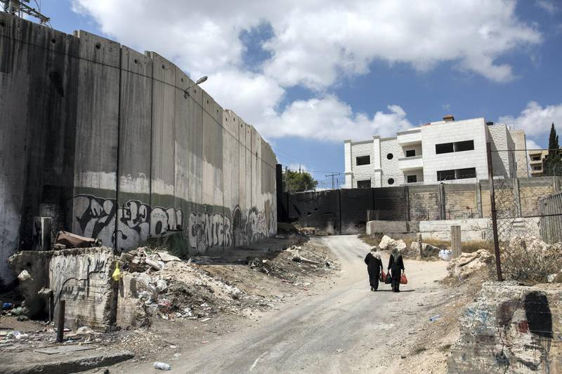 Palestinian women are seen walking along Israel's  8 meter high cement separation barrier on the West Bank side of the divided Palestinian village of Abu Dis on August 27,2018.(Photo by Heidi Levine for The National )