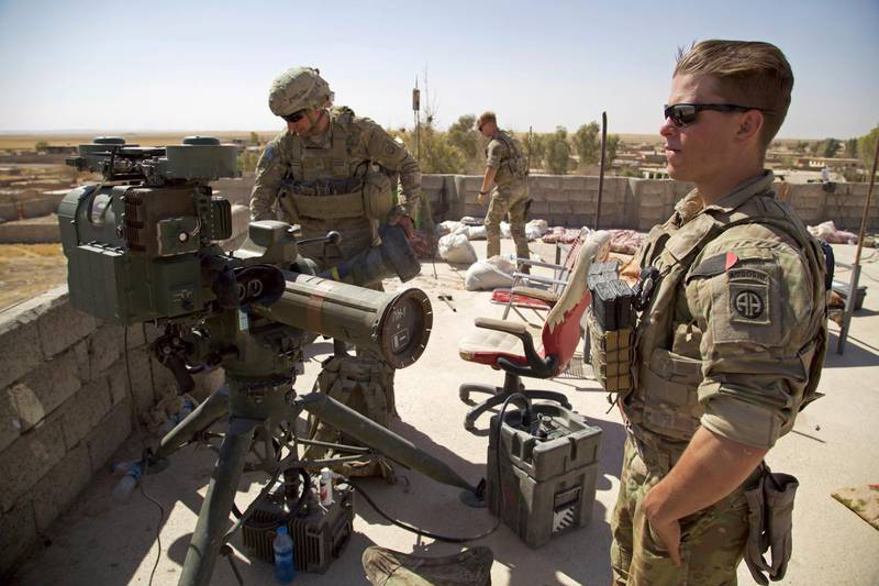 FILE - In this Aug. 20, 2017 file photo, U.S. Army soldiers stands next to a guided-missile launcher, a few miles from the frontline, in the village of Abu Ghaddur, east of Tal Afar, Iraq.  American troops have started to draw down from Iraq following Baghdad's declaration of victory over the Islamic State group last year, according to western contractors at a U.S.-led coalition base in Iraq. (AP Photo/Balint Szlanko, File)