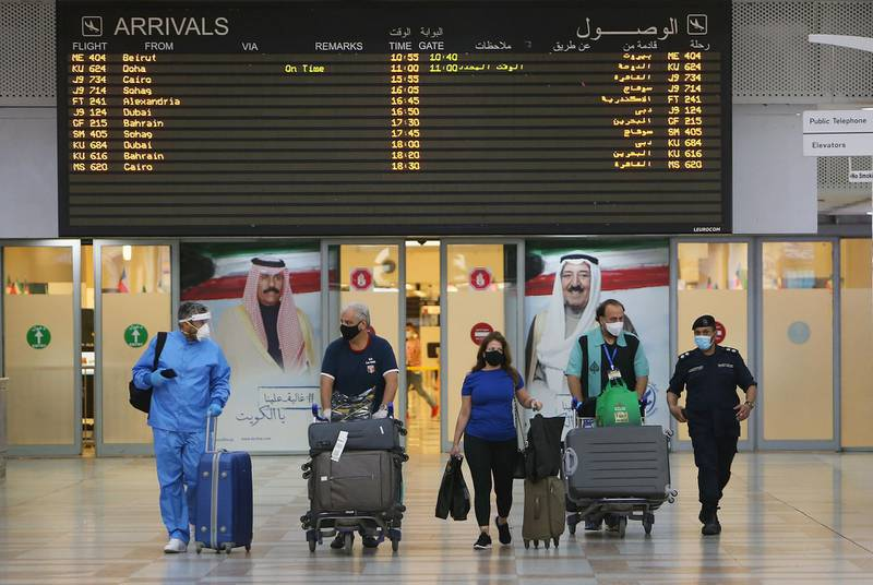 Travellers arrive at Kuwait international Airport, in Farwaniya, about 15kms south of Kuwait City, on August 1, 2020.  Commercial flights resumed at Kuwait International Airport today after months of shut down due to the COVID-19 pandemic. / AFP / YASSER AL-ZAYYAT