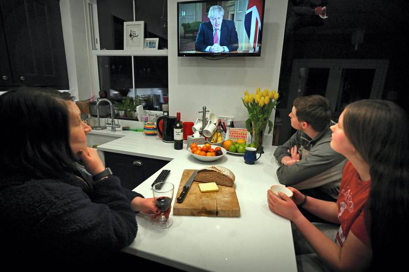 """Members of a family listen as Britain's Prime Minister Boris Johnson makes a televised address to the nation from inside 10 Downing Street in London, with the latest instructions to stay at home to help contain the Covid-19 pandemic, from a house in Liverpool, north west England on March 23, 2020. - Britain on Monday ordered a three-week lockdown to tackle the spread of coronavirus, shutting """"non-essential"""" shops and services, and banning gatherings of more than two people. """"Stay at home,"""" Prime Minister Boris Johnson said in a televised address to the nation, as he unveiled unprecedented peacetime measures after the death toll climbed to 335. (Photo by Paul ELLIS / AFP)"""
