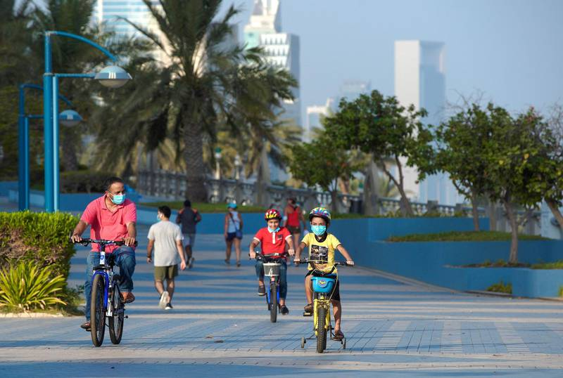 Abu Dhabi, United Arab Emirates, July 10, 2020.    A father and his son's enjoy a bike ride along the Corniche on a Friday morning.Victor Besa  / The NationalSection:  StandaloneReporter: