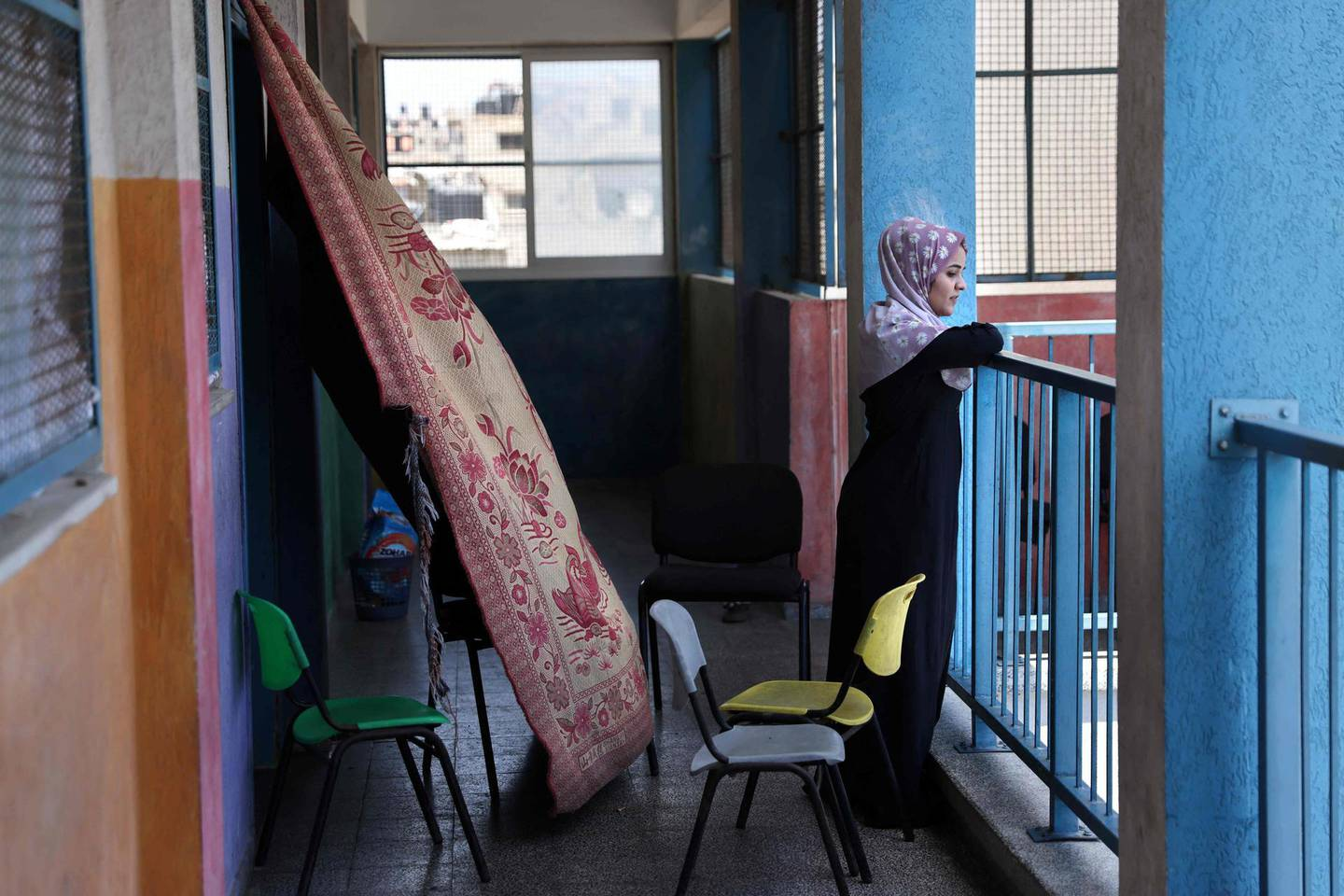 A member from the Abu Ghadyan Palestinian family is pictured on the balcony of a school run by the United Nations Relief and Works Agency for Palestine Refugees (UNRWA) where she will be living temporarily with her relatives, after their home was damaged during the recent Israeli bombing in Gaza City, on May 29, 2021, more than a week after a ceasefire brought an end to 11 days of hostilities between Israel and Hamas.  / AFP / THOMAS COEX