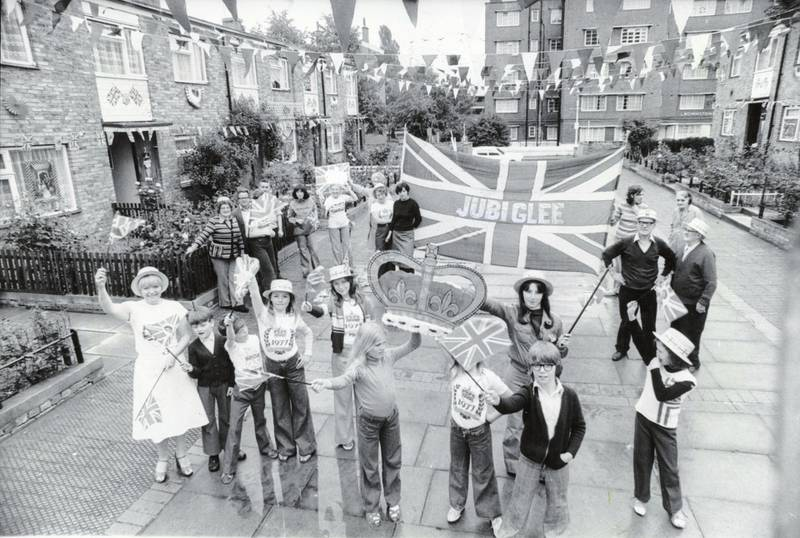 Residents in St Matthews Road, Brixton after they won a competition for the best decorated street to celebrate the Silver Jubilee of Queen Elizabeth II, south London, 10th June 1977. They have apparently coined the word 'Jubiglee', which is sewn onto their large Union Flag. (Photo by Douglas Doig/Evening Standard/Hulton Archive/Getty Images)