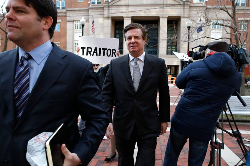 """FILE - In this March 8, 2018, file photo, Jason Maloni, left, former Trump campaign chairman Paul Manafort's spokesman, left, walks with Paul Manafort, center, as they leave the Alexandria Federal Courthouse after an arraignment hearing in Alexandria, Va. A federal judge in Virginia has rejected Manfort's move to throw out charges brought by the special counsel in the Russia investigation. The decision June 26 was a setback for Manafort in his defense against numerous tax and bank fraud charges. Behind Manafort protester Bill Christeson holds up a sign that says """"traitor."""" (AP Photo/Jacquelyn Martin)"""